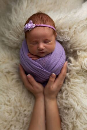 The concept of safety and happiness. Newborn baby girl is sleeping in a cocoon pose (potato bag) in his mothers arms