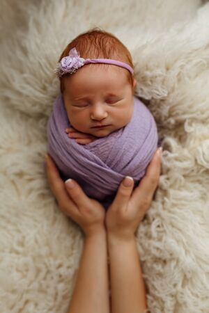 Newborn baby girl is sleeping in a cocoon pose (potato bag) in his mothers arms. The concept of safety and happiness