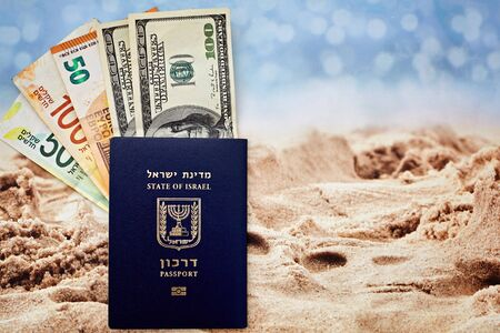 Israeli citizen international passport hundred dollar bills euro and shekels on sand and sea background, concept of odin and tourism