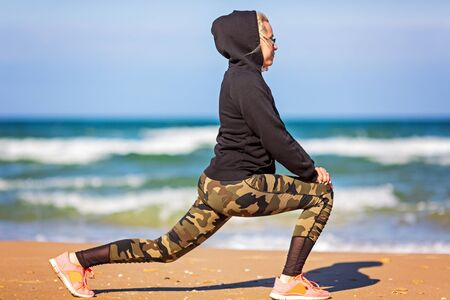 training concept crossfit fitness workout sport and lifestyle. Woman in hoodie, leggings . Healthy and sport concept. Outdoor sport activity