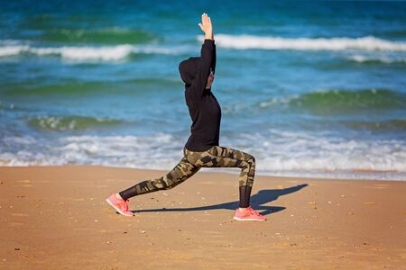 Girl in sportswear doing morning exercises on the beach. training concept crossfit fitness workout sport and lifestyle. Woman in hoodie, leggings. Healthy and sport concept. Outdoor sport activity