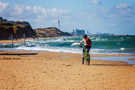 Cyclist with backpack on the carrier ridig along the sandy coast of the Gulf of Tel-Aviv