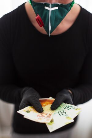 man in black gloves and a protective mask holds the Israeli currency one hundred and fifty shekels Reklamní fotografie