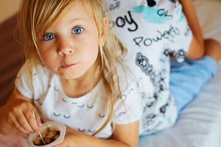 little blonde girl with blue eyes eats chocolate yogurt