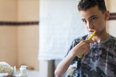 Portrait view of a young man brushing his teeth in a home bathroom, looking at his own reflection getting ready for school, home interior. Health and well being teeth care and grooming, indoors