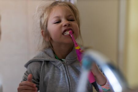 Emotional close up of a cute little girl brushing teeth with electric toothbrush 写真素材
