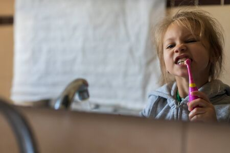 Emotional close up of a cute little girl brushing teeth with electric toothbrush. 写真素材