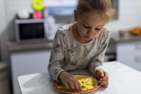 Beautiful little girl eating potato chips in the kitchen 写真素材