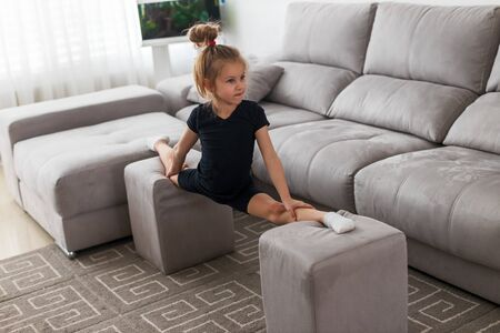 little gymnast in quarantine at home during an online lesson does splits on puffs