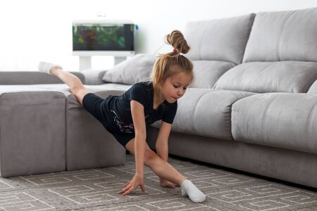 Performing full twine. Elastic little girl doing gymnastic on furniture in living room in bright daylight