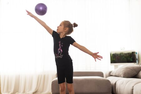 The girl does gymnastics at home. Gymnastics video tutorial. Gymnastic exercises. The idea for a childrens activity in quarantine