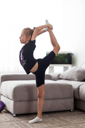 little girl does gymnastics at home doing stretching exercises 写真素材