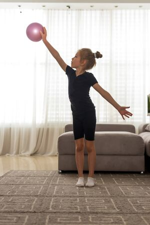 Blue-eyed girl Toddler does rhythmic gymnastics in a black bodysuit, plays with a pink ball on the home
