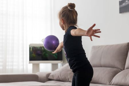 Girl gymnast performs exercises with the ball