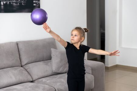 Little girl gymnast, performs various gymnastic and fitness exercises.