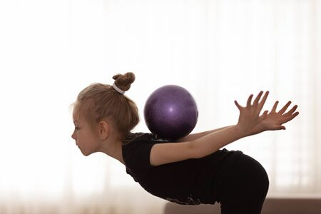 Beautiful little girl doing exercises with a fitness ball. Sport and healthy lifestyle concept.