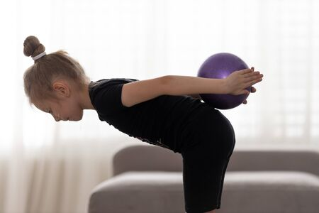Flexible cute little girl child gymnast doing acrobatic exercise with ball. Sport, training, fitness, active lifestyle concept