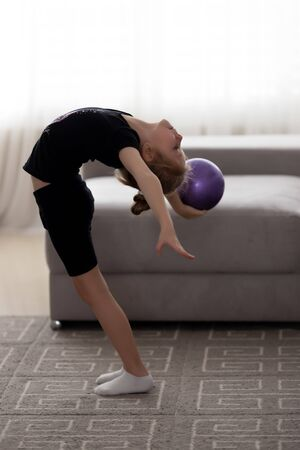 Exercises with gymnastic ball. Little girl performs gymnastic tricks with ball