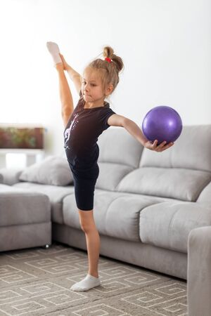 girl in a tracksuit doing exercises with ball. Healthy lifestyle concept, sports uniforms, world Cup, specialized clothing, uniforms