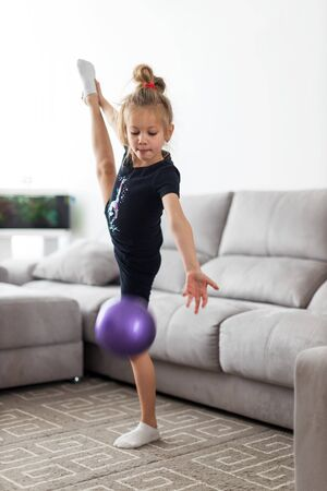 Little girl gymnast, performs various gymnastic and fitness exercises. The concept of childhood and sport, a healthy lifestyle 写真素材