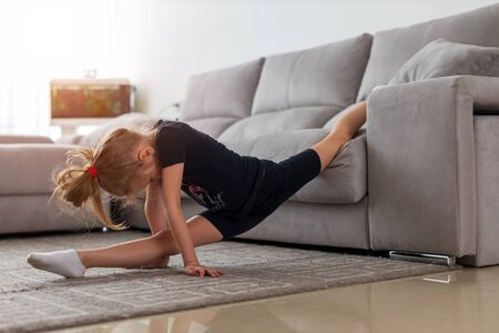 Morning exercises. Cute gymnast practice stretching every morning. Girl child stretching on carpet. Time for morning stretching. Girl kid blonde hair sportswear stretching