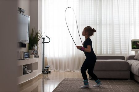 Happy little girl jumping over the rope at home during the isolation. The bright sun illuminates the room 写真素材