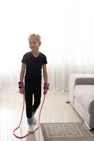 Happy little girl jumping over the rope at home during the isolation. The bright sun illuminates the room. 写真素材