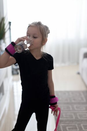 Little girl in a black bathing suit drinking water after hard physical exercises
