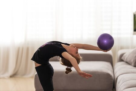 Little girl gymnast performs various gymnastic and fitness exercises at home. The concept of childhood and sport