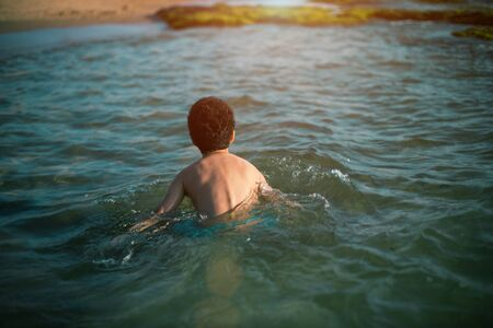 back view photo of cote child boy playing on the beach on summer holidays. Happy child playing in the sea