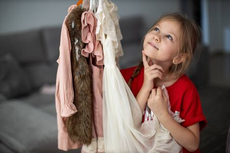Kid thinking what to choose to wear in front of many choices of dresses on hangers