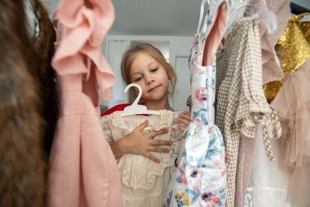 Cute little girl choosing clothes in dressing room 写真素材