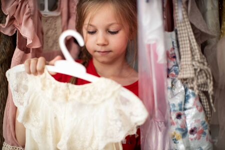 Little child girl choosing her clothes. Kid thinking what to choose to wear in front of many choices of dresses on hangers