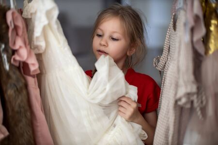 Soft Focus of a 5-6 Years Old Child Choosing her own Dresses from Kids Cloth Rack in Clothing Shop. Shopaholics Girl