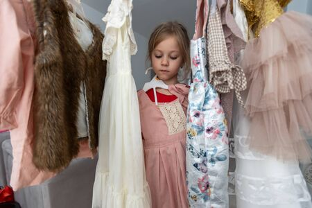 Laughing girl stands between hangers with dresses. High quality photo 写真素材