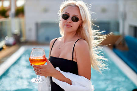 Beautiful woman enjoying by the swimming pool with cocktail
