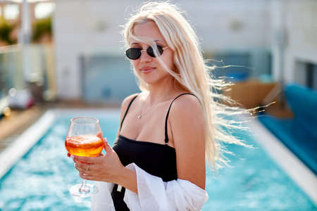 Attractive young woman wearing bikini, sunglasses, standing on the swimming pool, drinking cocktails