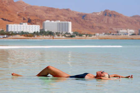 Young woman floating on surface of Dead Sea, Israel, enjoy her vacation during sunset time in summer