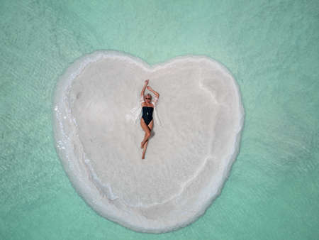 Journey to the shores of the Dead Sea. Shooting from the drone. bather relaxing on a heart-shaped island in the Dead Sea