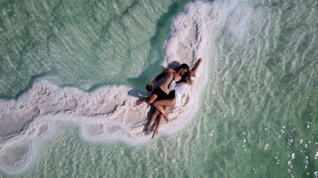 couple of tourists rest and lie in an embrace on the shore of the Dead Sea Stok Fotoğraf