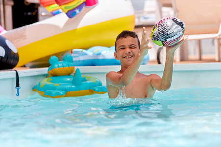 Boy playing with balls at the pool Stock fotó