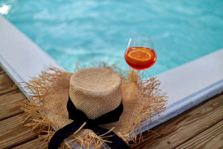 Cocktail glass in front of a straw hat placed on a wooden boardwalk by the sea. Summer vacation concept with beach accessories