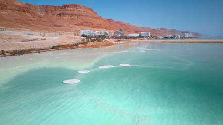 Blue water of Dead sea, desert coastline, aerial view. Salt crystals on the surface of Dead sea, Israel