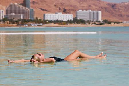 Young woman is relaxing in dead sea Stock fotó