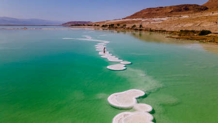 loving couple is resting on the dead sea. Salt coastline, The sea in Israel dies out and dries up