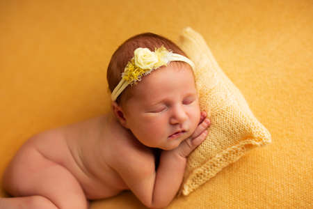 portrait of a beautiful seven day old baby girl. She is sleeping in a curled up fetal position on a yellow blanket