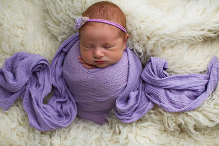 Sleeping, nine day old newborn baby girl swaddled in a purple wrap. Shot in the studio on purple material Stok Fotoğraf