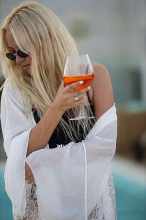 Woman with glass of refreshing drink dancing near swimming pool
