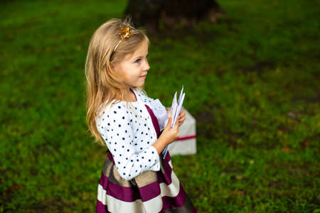 little girl with a crown on her head in festive clothes holds gift envelopes in her hands Stok Fotoğraf
