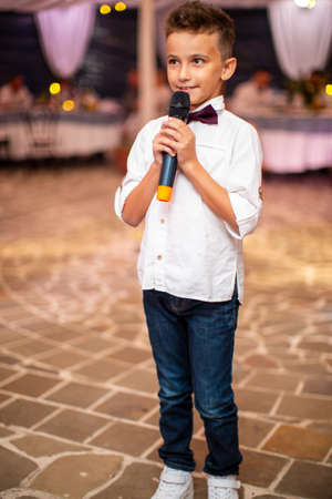 Cute little boy with microphone singing for guests at the holiday